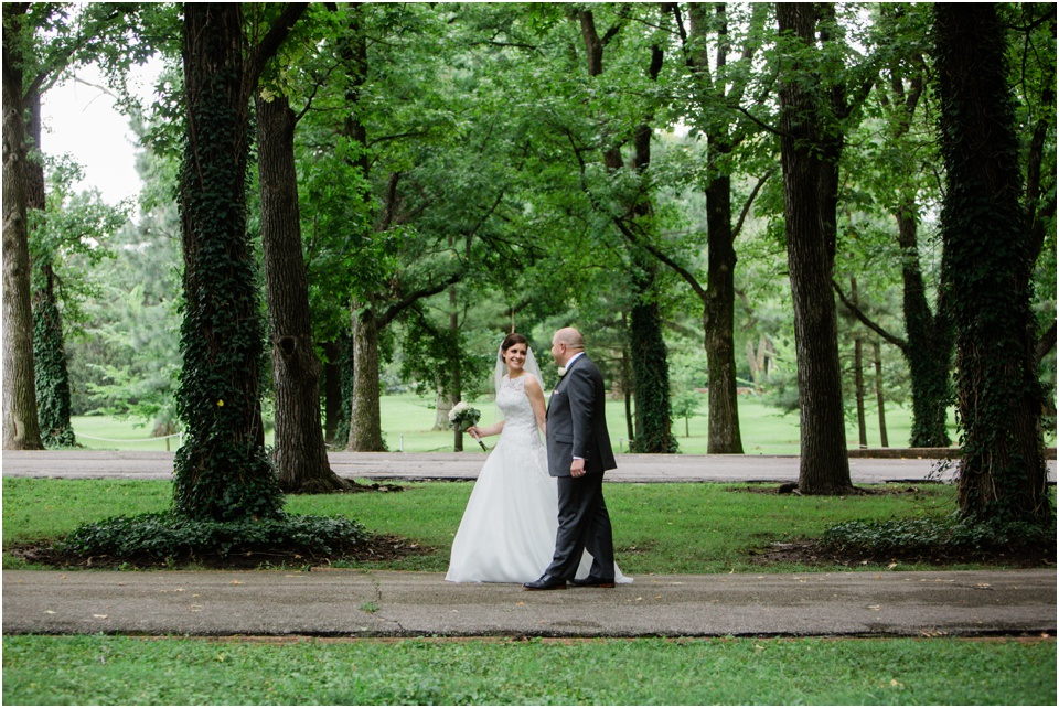 Bride and groom walking through Tower Grove Park