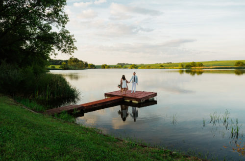 Bride and groom on a dock at sunset